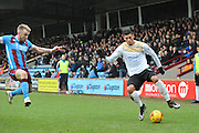 Matthew Briggs of colchester United tries to cross the ball past Paddy Madden of Scunthorpe United  during the Sky Bet League 1 match between Scunthorpe United and Colchester United at Glanford Park, Scunthorpe, England on 23 January 2016. Photo by Ian Lyall.