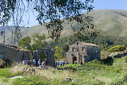 Tourists visiting Skordilis Mansion house ruin in oldest town of Corfu - ancient Old Perithia - Palea Perithea, Greece