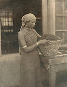 Woman with basket of tea leaves.<br /> Photograph by Skeen.