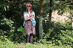 Image ©Licensed to i-Images Picture Agency . 17/07/2014 . Henham Park , Suffolk , United Kingdom. A woman takes shelter amongst the shade of some trees as temperatures soar in to the late 20s degrees centigrade in Suffolk at The Latitude Festival of music and arts . Picture by Joel Goodman/i-Images