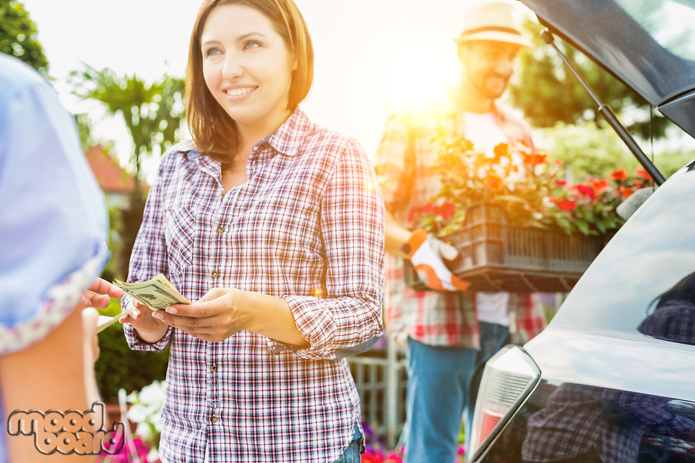 Female customer giving cash payment to the shop owner against mature gardener putting flowers on car trunk
