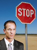 Businessman standing next to stop sign in desert head and shoulders