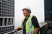 NEW YORK, NY – MAY 13, 2016: Simon Davison, 56, stands on the balcony of a building in Manhattan's financial district. As a project manager for a local construction firm, Davison thrives on the energy of the city. But when congestive heart failure threatened to derail his ability to keep up, he knew he had to get help. Davison's heart was functioning at only 15%, so he scheduled a procedure on Long Island at Stony Brook University Hospital. Now, thanks to the team at Stony Brook and his new Left Ventricular Assist Device, Davison is back on his feet and exploring the city he loves more than ever.