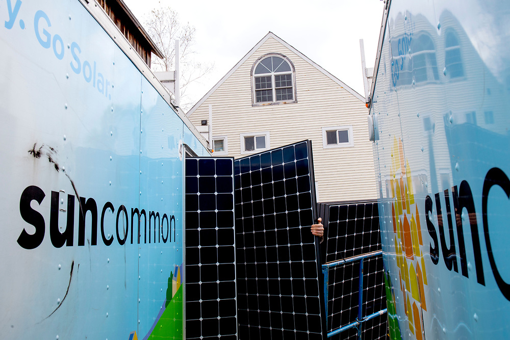 """Peck Electric subcontractor Andy Bartz pulls solar panels from a SunCommon storage trailer while installing a system at 4 Corners Farm in Newbury, Vt., on May 9, 2017. The crew has been busy traveling across Vermont to do installations. """"This is the first time in my career I've worked two years straight,"""" said electrician Jerry Houghton, who is nearing retirement. (Photo by Geoff Hansen)"""