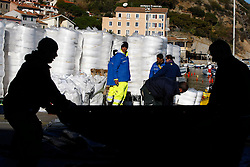 Oil recovery workers prepare oil protection barriers to place next to the Costa Concordia cruise ship which ran aground off the west coast of Italy at Giglio island January 26, 2012. <br /> REUTERS/Darrin Zammit Lupi (ITALY)