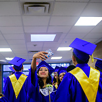 052215       Cable Hoover<br /> <br /> Rani Yamutewa steps out of line to take a selfie as she and the rest of the class of 2015 seniors line up for their commencement ceremony Friday at Zuni High School.