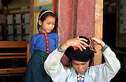 A child watches a Tai Dam woman adjust her headwear at an NGO handicraft sales project in the northern town of Muang Sing.
