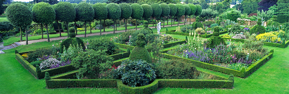 The East Garden. Pleached Lime avenue with pathway, Buxus sempervirens (Box) hedging parterre with topiary. Beds planted flowering perennials &amp; shrubs. Classical stone figurative sculpture. Boundary walls with planted urns. estate woodlands in the background.<br /> Hatfield House, Hatfield, Hertfordshire