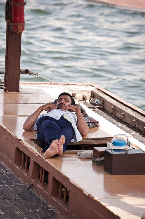 A man resting in an abra on the Dubai creek Archive of images of Dubai by Dubai photographer Siddharth Siva