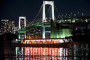 """The lights of a """"yakata-bune"""" pleasure boat are reflected in the calm waters of Tokyo Bay as it passes by Rainbow Bridge in Tokyo, Japan on 31 August  2010. .Photographer: Robert Gilhooly"""