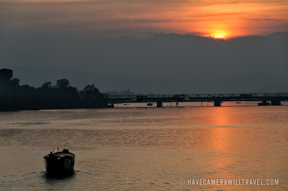 A boat makes its way up the Perfume River heading towards the setting sun in Hue, Vietnam.