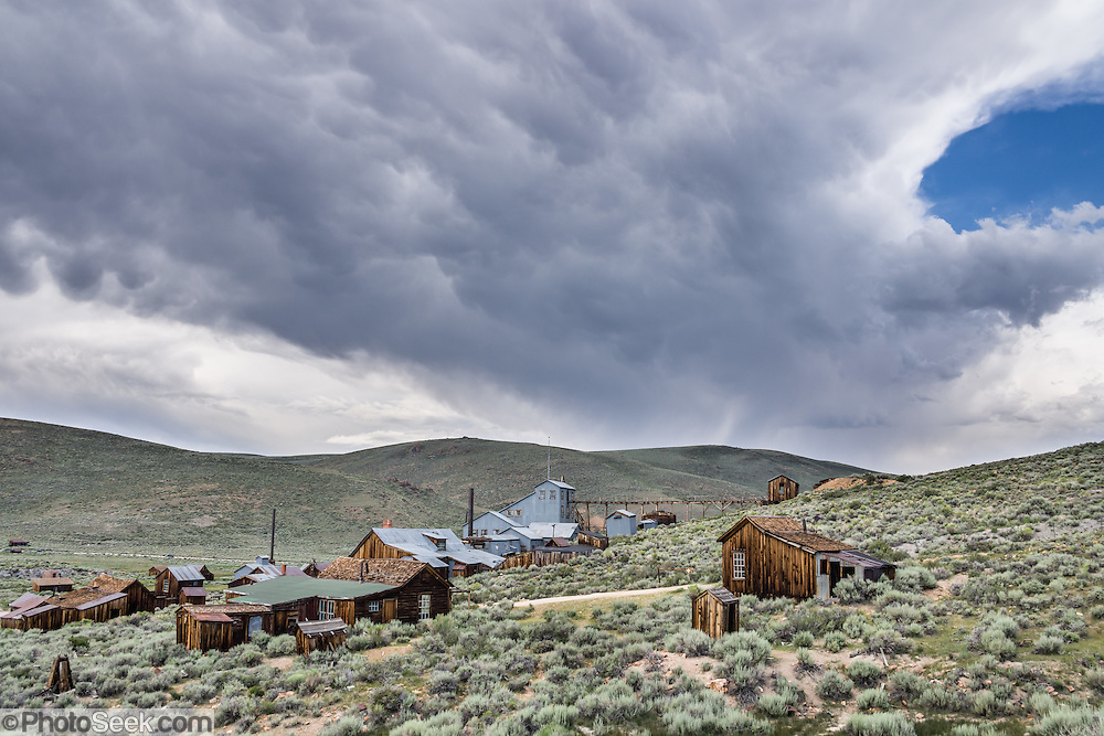 """Afternoon thunderstorm clouds loom over historic Bodie and its Standard Stamp Mill. Bodie is California's official state gold rush ghost town. Bodie State Historic Park lies in the Bodie Hills east of the Sierra Nevada mountain range in Mono County, near Bridgeport, California, USA. After W. S. Bodey's original gold discovery in 1859, profitable gold ore discoveries in 1876 and 1878 transformed """"Bodie"""" from an isolated mining camp to a Wild West boomtown. By 1879, Bodie had a population of 5000-7000 people with 2000 buildings. At its peak, 65 saloons lined Main Street, which was a mile long. Bodie declined rapidly 1912-1917 and the last mine closed in 1942. Bodie became a National Historic Landmark in 1961 and Bodie State Historic Park in 1962."""