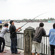 Four men fishing from the banks of the Saigon River in Ho Chi Minh City, Vietnam.