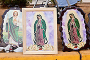"Dec. 12, 2009 -- PHOENIX, AZ: Religious pictures, including some of the Virgin of Guadalupe, for a sale during a procession to honor the Virgin of Guadalupe at St. Catherine of Siena Catholic Church in Phoenix, AZ. Most of the members of the church are Hispanic and Dec. 12, Virgin of Guadalupe Day, is one of the church's most important holy days. The Virgin of Guadalupe appeared to Juan Diego, a Mexican peasant, on Dec 9, 1531, on a hillside near Mexico City. She is the ""Queen of Mexico"" and ""Empress of the Americas"" and revered throughout Latin America.  Photo by Jack Kurtz"