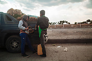 Huixcolotla, Mexico – March 27, 2017: Two men sell stolen gasoline inside of a wholesale market.