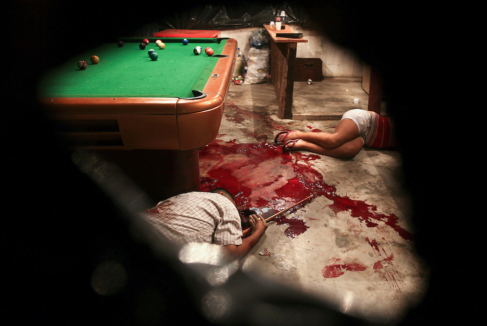 In this March 11, 2012 photo, the bodies of Lesbia Altamirano and Wilmer Orbera lie on the floor of a pool hall after being attacked by unidentified masked assailants in Choloma on the outskirts of San Pedro Sula, Honduras. A wave of violence has made Honduras among the most dangerous places on Earth, with a homicide rate roughly 20 times that of the U.S. rate, according to a 2011 United Nations report.