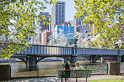 Couple Sitting on a Bench in Front of the Sandridge Bridge over the Yarra River
