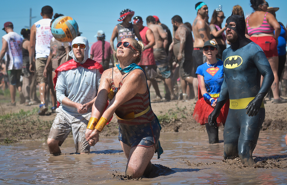"mkb060317a/metro/Marla Brose --  Nicole Goodreau, dressed as Wonder Woman, gets ready to hit the bump the ball as she plays mudd volleyball with her team, all dressed as super heroes, from UNM Hospital, during the Carrie Tingley Hospital Foundation's 23rd annual Mudd Volleyball tournament, Saturday, June 3, 2017. ""It's such a cool way to raise money,"" said Jenny Dillow, dressed as Supergirl, second from right, who played with her husband Nels Dahlgren, who came as Batman, right. (Marla Brose/Albuquerque Journal)"
