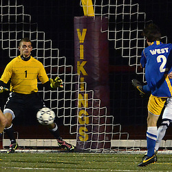 Photos by Tom Kelly IV<br /> West's Cameron Young (2) shoots and scores against Rustin goalkeeper Justin Davis (1) during the Downingtown West vs West Chester Rustin boys District One semifinal soccer game which was held Wednesday night October 30, 2013 at West Chester East High School.