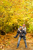 A happy couple, outside for a walk, enjoy Autumn colors on one of Courtenay's many walkway's that abound in the Comox Valley.  Courtenay, The Comox Valley, Vancouver Island, British Columbia, Canada.