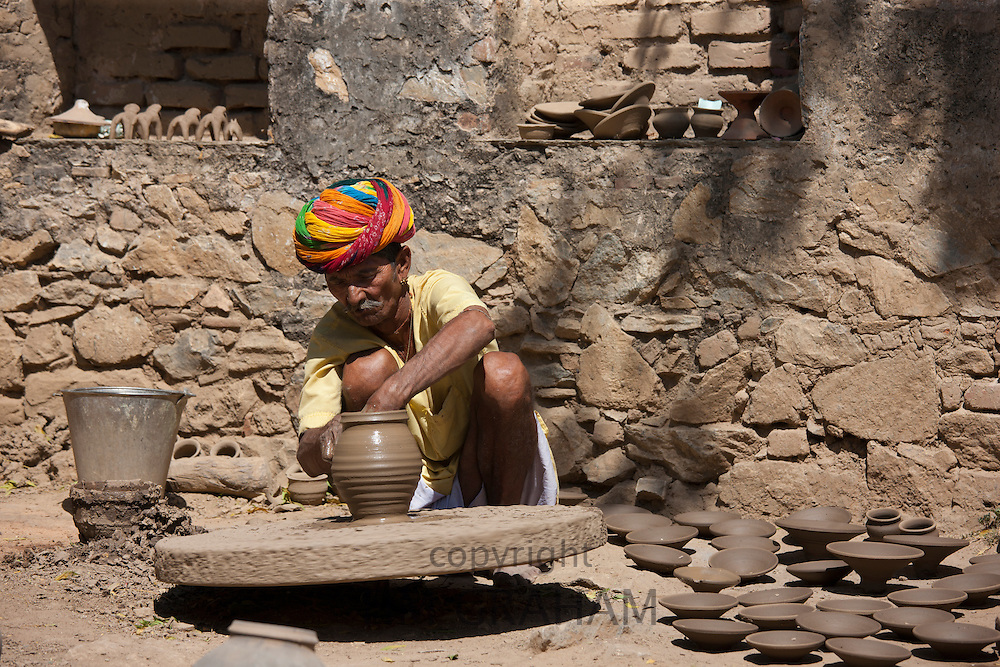 Potter in traditional Rajasthani turban works on potter's wheel at home making clay pots in Nimaj village, Rajasthan, India