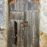 Old weathered wooden door with rusty lock, Scopello, Sicily, Italy