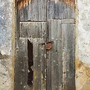 Old weathered wooden door with rusty lock, Scopello, Sicily, Italy