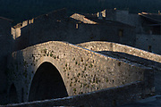 Dawn light on the stone hump-backed bridge in the pretty medieval walled village of Lagrasse, on 23rd May, 2017, in Lagrasse, Languedoc-Rousillon, south of France. Lagrasse is listed as one of France's most beautiful villages and lies on the famous Route 20 wine route in the Basses-Corbieres region dating to the 13th century.