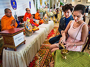 """14 FEBRUARY 2017 - BANGKOK, THAILAND:  Buddhist monks blesses a couple's marriage during a mass wedding in the Bang Rak district in Bangkok. Bang Rak is a popular neighborhood for weddings in Bangkok because it translates as """"Village of Love."""" (Bang translates as village, Rak translates as love.) Hundreds of couples get married in the district on Valentine's Day, which, despite its Catholic origins, is widely celebrated in Thailand.     PHOTO BY JACK KURTZ"""
