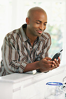 Smiling man using mobile phone at home