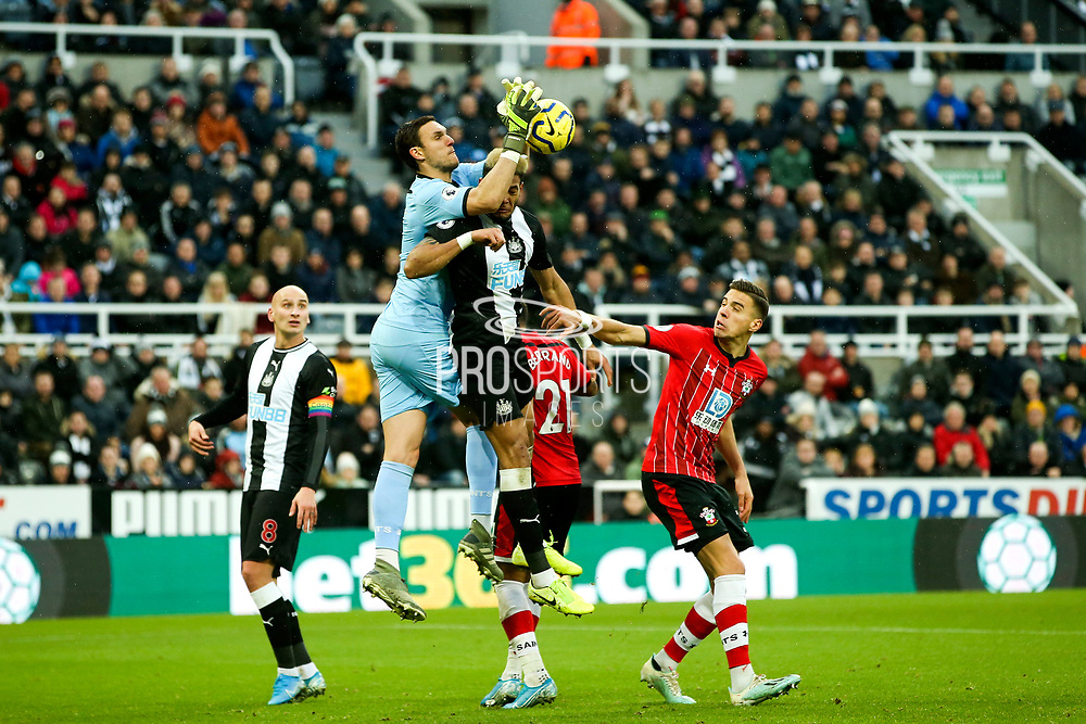 Alex McCarthy (#1) of Southampton stretches over the head of Joelinton (#9) of Newcastle United to punch the ball to safety during the Premier League match between Newcastle United and Southampton at St. James's Park, Newcastle, England on 8 December 2019.