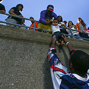 Brendan Porter #3 of the Boston Cannons grabs a baby that was dangled down to him from the stands following the game at Harvard Stadium on July 19, 2014 in Boston, Massachusetts. (Photo by Elan Kawesch)