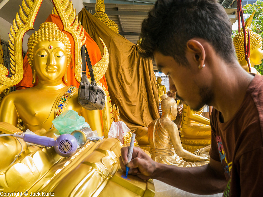 "12 NOVEMBER 2012 - BANGKOK, THAILAND:   A worker details a statue of the Buddha at a workshop Bamrung Muang Street in Bangkok. Thanon Bamrung Muang (Thanon is Thai for Road or Street) is Bangkok's ""Street of Many Buddhas."" Like many ancient cities, Bangkok was once a city of artisan's neighborhoods and Bamrung Muang Road, near Bangkok's present day city hall, was once the street where all the country's Buddha statues were made. Now they made in factories on the edge of Bangkok, but Bamrung Muang Road is still where the statues are sold. Once an elephant trail, it was one of the first streets paved in Bangkok. It is the largest center of Buddhist supplies in Thailand. Not just statues but also monk's robes, candles, alms bowls, and pre-configured alms baskets are for sale along both sides of the street.    PHOTO BY JACK KURTZ"