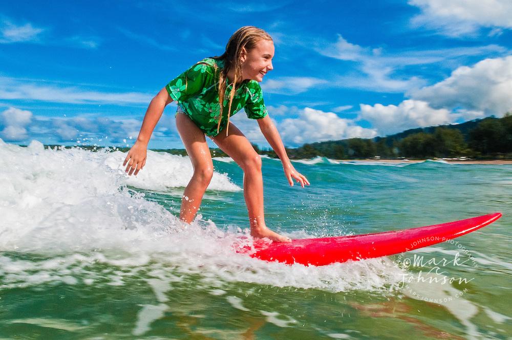 8 year old girl surfing at Hanalei Bay, Kauai, Hawaii