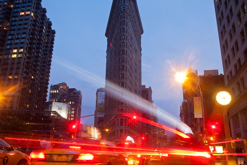 Traffic streaks down 5th Avenue next to the Flat Iron Building at dusk, New York City, USA