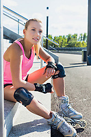 Portrait of young attractive woman sitting while wearing safety gear and rollerblades