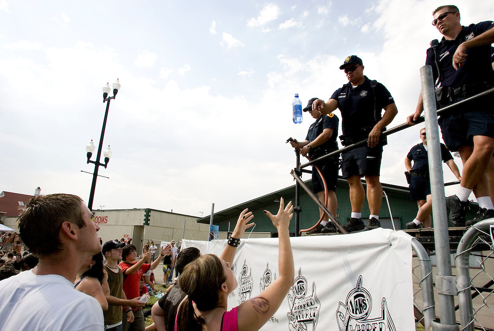 Officer Shaun Wihongi of the Salt Lake Police Department tosses a bottle of water to a fan after filling it up police tried to help them stay cool as they watch the many bands and other attractions at the Van's Warped Tour stop at the Utah State Fair Park in Salt Lake Cityi, Utah Saturday July 7, 2007.  August Miller/ Deseret Morning News