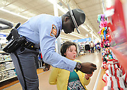 Becky Cuzzort, 9, reacts as Georgia State Trooper James Houston shows her a necklace during the Cops and Kids event at Walmart on Thursday in Buford. (Staff Photo: David Welker)