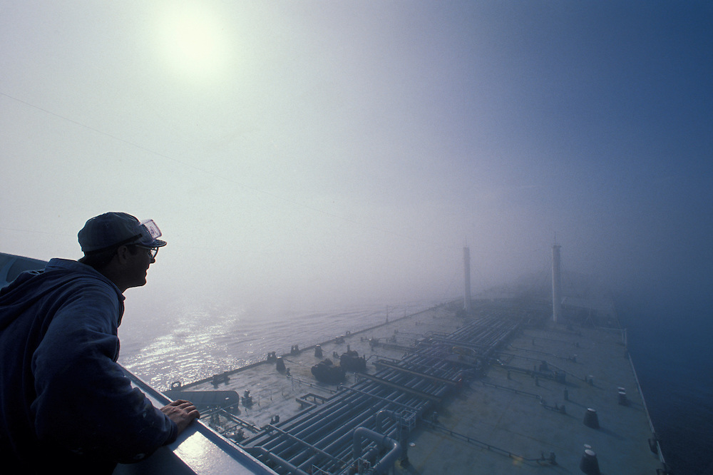 USA, Alaska, Crewman stands watch on bridge as tanker Arco Juneau sails through fog in Prince William Sound