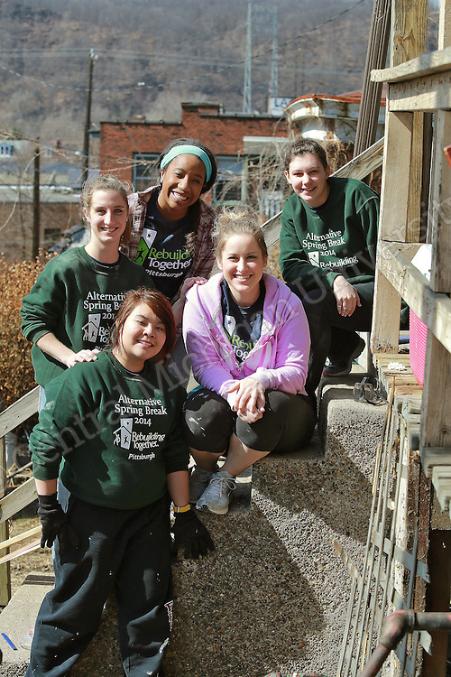 Clockwise from lower left: Elaine Trinh, of Grand Rapids, Ashley Popp, of Bay City, Adrianne Bright, of Flushing, Samantha Bruck, of Monroe, and Katie Wojewoda, of Caro take a break from their urban renewal project. They were among ten Central Michigan University students who spent their Alternative Break week volunteering with Rebuilding Together, an urban renewal experience, in Pittsburgh, PA. Their urban renewal experience gave them hands on experience working on homes and making repairs. Photo by Steve Jessmore/Central Michigan University