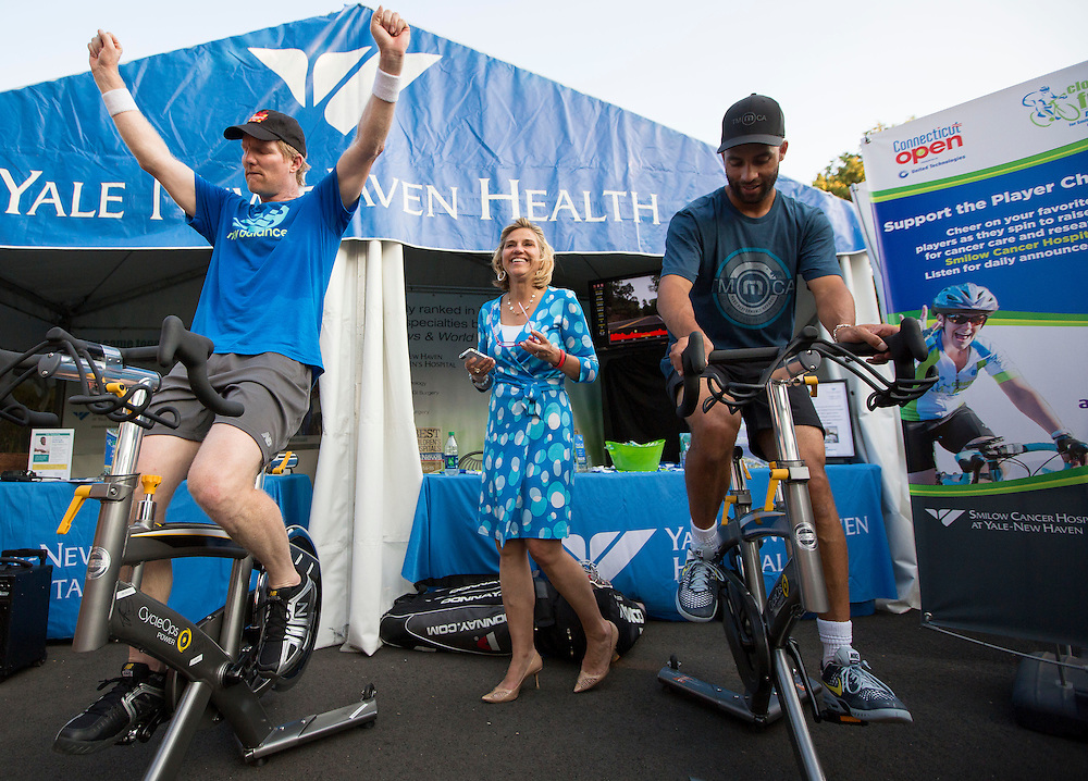 August 20, 2014, New Haven, CT:<br /> Jim Courier and James Blake ride spin bikes at the Yale New Haven Health booth during the Men's Legends Event on day six of the 2014 Connecticut Open at the Yale University Tennis Center in New Haven, Connecticut Wednesday, August 20, 2014.<br /> (Photo by Billie Weiss/Connecticut Open)