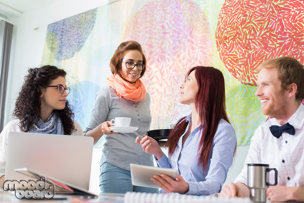 Businesswoman giving coffee to female colleague in creative office