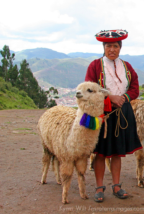 Americas, South America, Peru.  Woman in traditional dress stands with llama in the Andes.