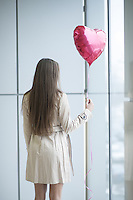 Woman with back to camera holding heart shaped balloon