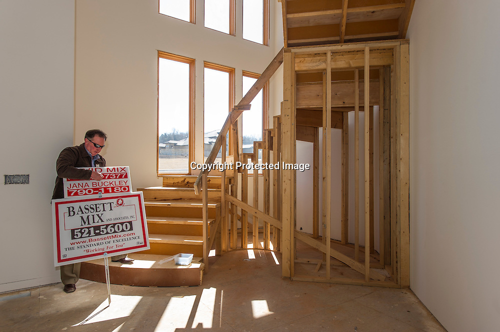 David Mix with Bassett Mix Real Estate adjusts a sign while standing inside 3487 Horse Meadow Drive in Fayetteville, on Monday, March 10, 2014.<br /> <br /> Photo by Beth Hall