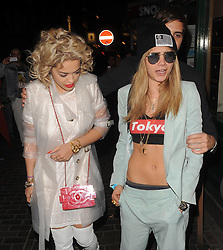 Rita Ora and Cara Delevingne enjoy a night out at The Box Club in Soho London. Rita was wearing see-through raincoat, white dress,  thigh high boots. Cara Delevingne was dress dressed in a mint suit, belly top and a gold chain the the initial (R). London, UK. 30/04/2013<br />