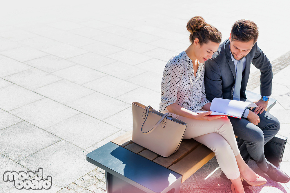Young attractive businessman discussing business plans over document with beautiful businesswoman while sitting on bench against office building