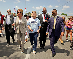 29 August 2015. Lower 9th Ward, New Orleans, Louisiana.<br /> Hurricane Katrina 10th anniversary memorials.  <br /> Former Louisiana senator Mary Landrieu (blue T-shirt) and Congresswoman Nancy Pelosi (pant suit) join local politicians attending the memorial for victims and survivors of the storm. <br /> Photo credit©; Charlie Varley/varleypix.com.