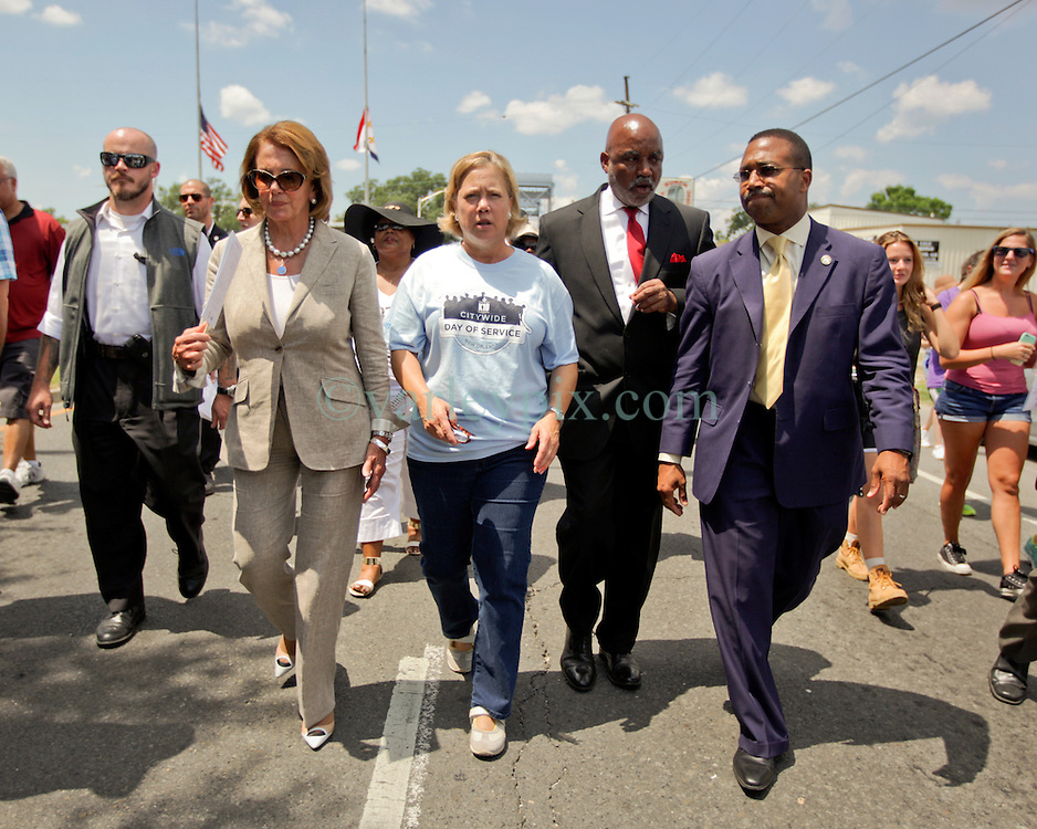 29 August 2015. Lower 9th Ward, New Orleans, Louisiana.<br /> Hurricane Katrina 10th anniversary memorials.  <br /> Former Louisiana senator Mary Landrieu (blue T-shirt) and Congresswoman Nancy Pelosi (pant suit) join local politicians attending the memorial for victims and survivors of the storm. <br /> Photo credit&copy;; Charlie Varley/varleypix.com.