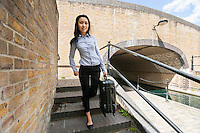 Full length portrait of young businesswoman with luggage walking down stairs